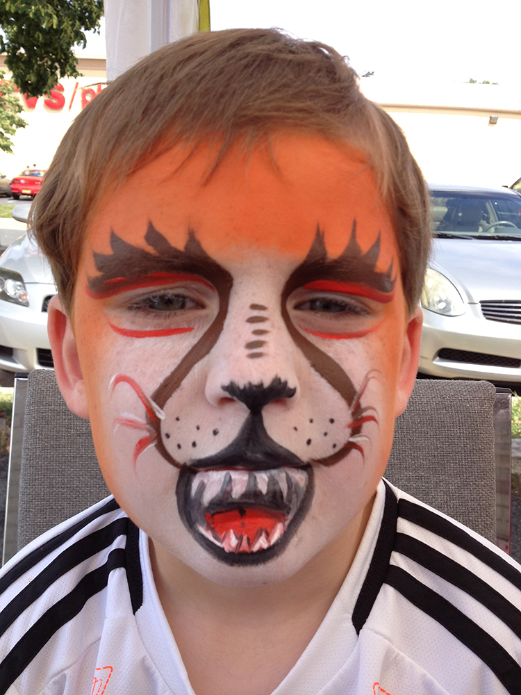 Boy with a tiger painted on his face