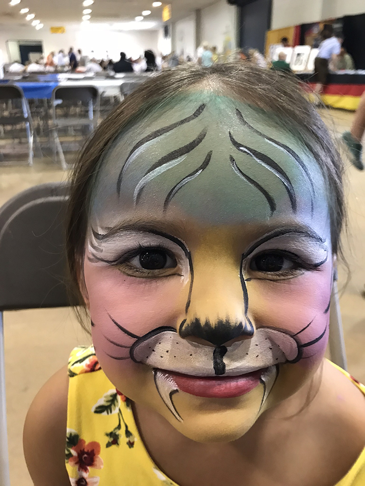 Girl with her face painted like a tiger