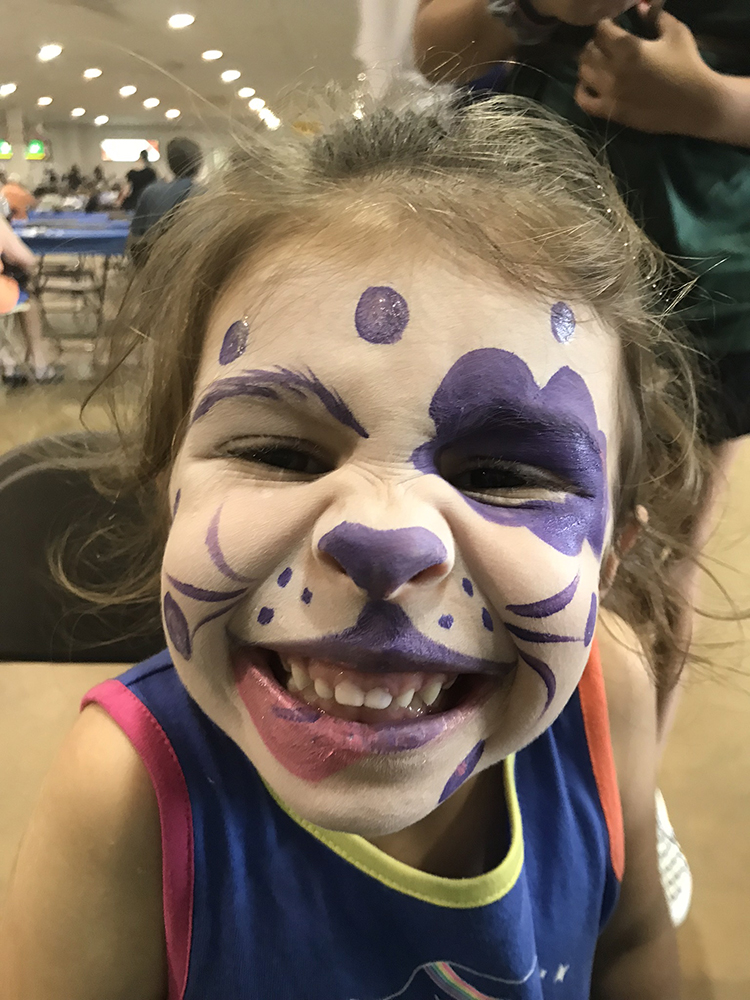 Girl with a puppy dog painted on her face