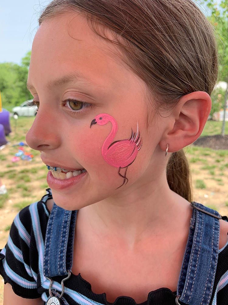 Girl with a flamingo painted on her face