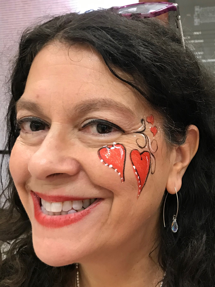 Woman with two hearts painted on her cheek