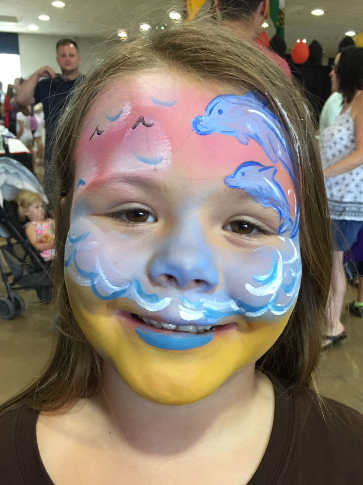 Girl with dolphins painted on her face