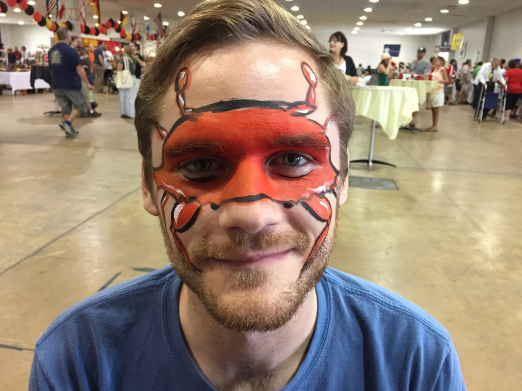 Man with a crab painted on his face