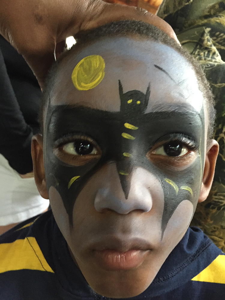 Boy painted with a Batman mask