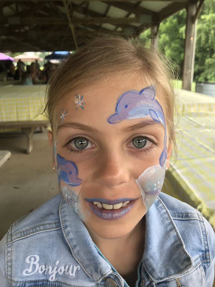 Girl painted with Dolphins on her face