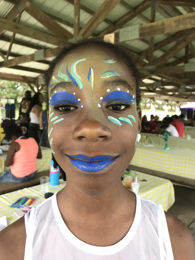 Girl painted with a seascape on her face